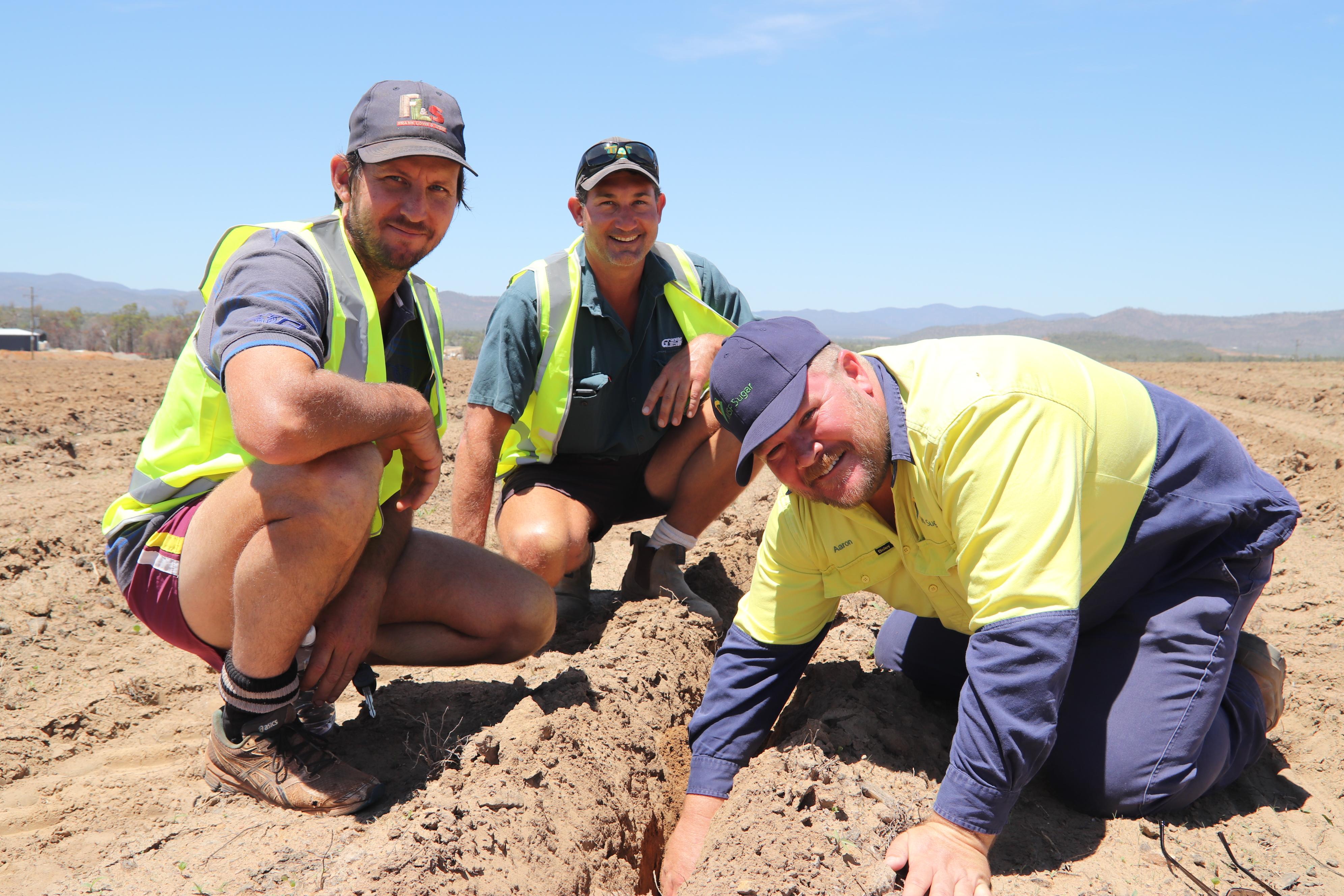 Growers Jason Hampson (Mena Creek), David Srhoj (Mareeba) and MSF Sugar irrigation specialist Aaron Moore inspect the development of sub-surface drip irrigation.