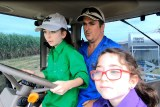 Frank Mugica and his daughters sitting in the cab of a tractor.