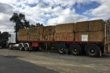 "A truck carrying hay bails painted with the slogan ""farms for food not power"" is parked outside a community meeting in Culcairn"